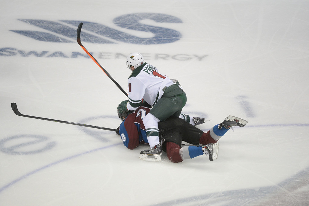 . Zach Parise (11) of the Minnesota Wild falls on top of Paul Carey (28) of the Colorado Avalanche during the first period of action. (Photo by Karl Gehring/The Denver Post)