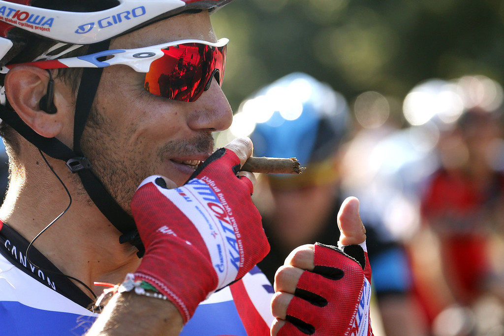 . Spain\'s Joaquim Rodriguez Oliver pretends to smoke a cigare to celebrate his third-placed in the overall standings as he rides at the start of the 133.5 km twenty-first and last stage of the 100th edition of the Tour de France cycling race on July 21, 2013 between Versailles and Paris.  JOEL SAGET/AFP/Getty Images