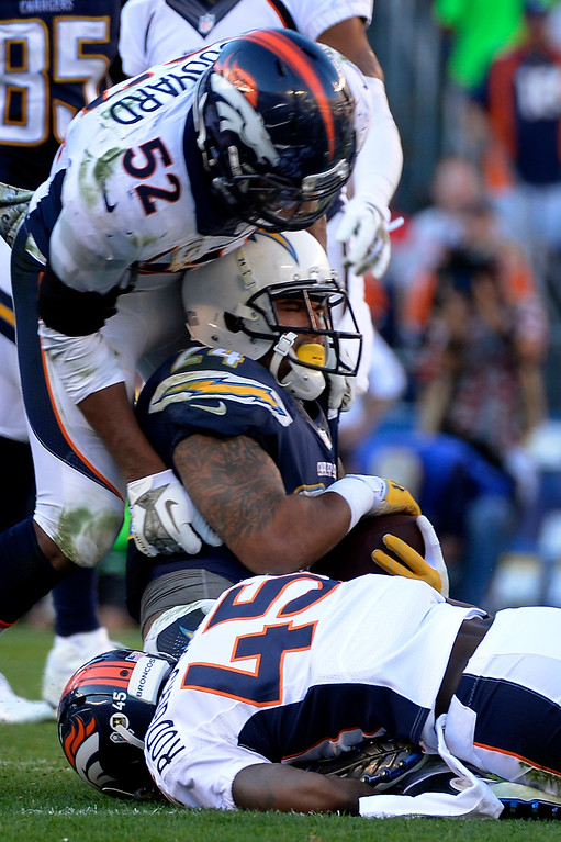 . Outside linebacker Wesley Woodyard #52 of the Denver Broncos and cornerback Dominique Rodgers-Cromartie #45 stop running back Ryan Mathews #24 of the San Diego Chargers at Qualcomm Stadium November 10, 2013 San Diego, CA. (Photo By Joe Amon/The Denver Post)
