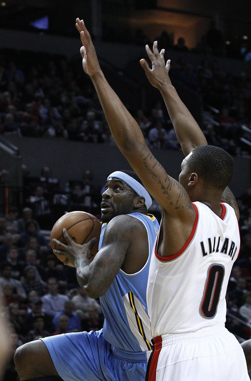 . Denver Nuggets guard Ty Lawson, left, drives to the basket against Portland Trail Blazers guard Damian Lillard during the first quarter of an NBA basketball game, Thursday, Dec. 20, 2012, in Portland, Ore. (AP Photo/Don Ryan)