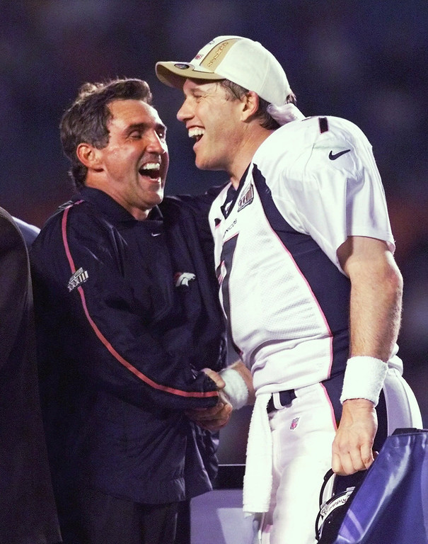 . Denver Broncos quarterback John Elway, right, and head coach Mike Shanahan laugh on the victory stand following their 34-19 win over the Atlanta Falcons in Super Bowl XXXIII in Miami, Sunday, Jan. 31, 1999. (AP Photo/Amy Sancetta)