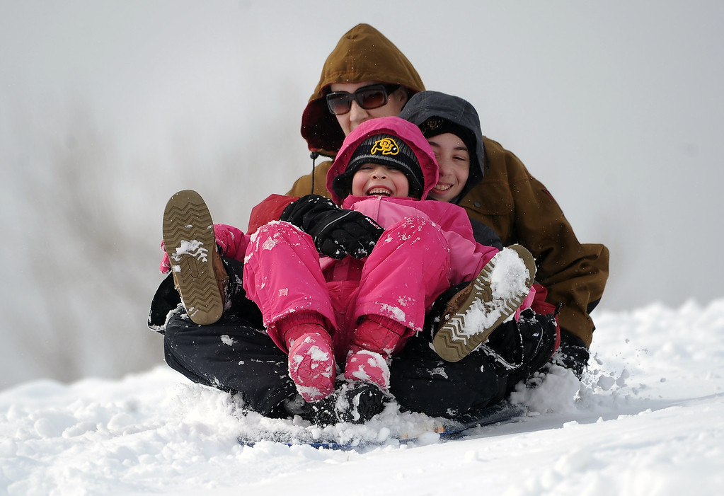 . Laurel Brown, 6, in pink, her brother, 12, and mother Stephanie, of Boulder, laugh as they try to race down the sledding hill.  Kids of all ages enjoyed sledding down a gently sloping hill in Scott Carpenter Park in Boulder on February 21, 2012.  Between 4-6 inches of freshly fallen snow created havoc on the metro area roadways but loads of fun for kids with a day off from school.   (Photo By Helen H. Richardson/ The Denver Post)