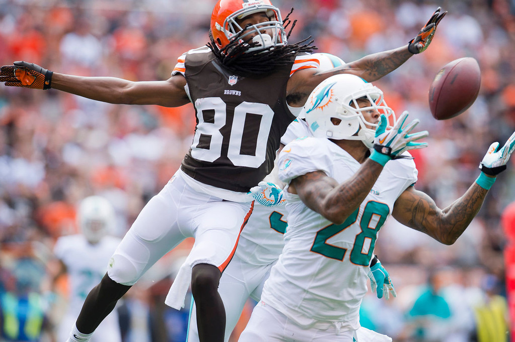 . Wide receiver Travis Benjamin #80 of the Cleveland Browns tries to prevent the interception by cornerback Nolan Carroll #28 of the Miami Dolphins during the first half at First Energy Stadium on September 8, 2013 in Cleveland, Ohio. (Photo by Jason Miller/Getty Images)