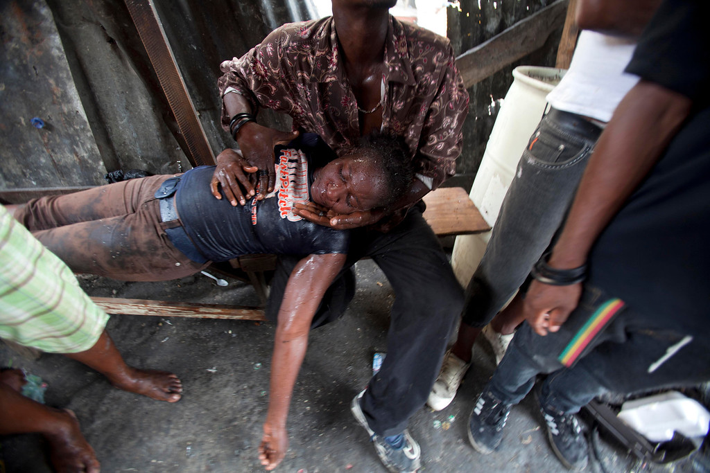. In this Monday, Sept. 30, 2013 photo, people help a street vendor who passed out from tear gas exposure, fired by police breaking up a protest in Port-au-Prince, Haiti. Riot police broke up the end of an anti-government demonstration by people marking the anniversary of the 1991 ouster of former President Jean-Bertrand Aristide. (AP Photo/Dieu Nalio Chery)