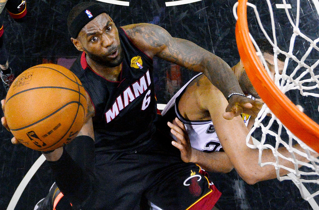. Miami Heat forward LeBron James shoots over San Antonio Spurs forward Tim Duncan (21) during the first half in Game 2 of the NBA basketball finals on Saturday, Nov. 8, 2014, in San Antonio. (AP Photo/Larry W. Smith, pool)