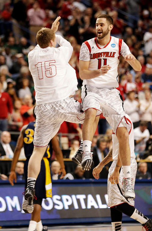. Louisville\'s Luke Hancock (11) and Tim Henderson (15) celebrate during the second half of a second-round game in the NCAA college basketball tournament against the North Carolina A&T Thursday, March 21, 2013, in Lexington, Ky. (AP Photo/John Bazemore)