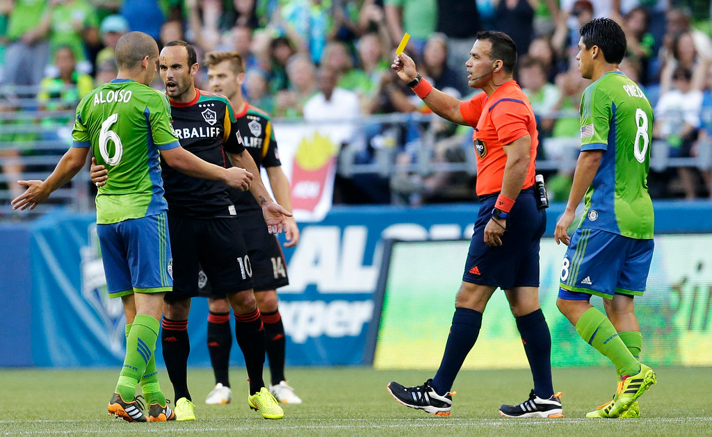 . Los Angeles Galaxy\'s Landon Donovan, second from left, is booked with a yellow card by referee Hilario Grajeda, second from right, after Donovan fouled Seattle Sounders\' Osvaldo Alonso, left, in the first half of an MLS soccer match, Monday, July 28, 2014, in Seattle. (AP Photo/Ted S. Warren)