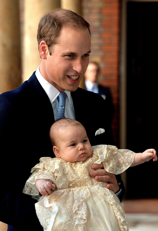 . Britain\'s Prince William, Duke of Cambridge holds his son, Prince George of Cambridge, as he arrives at Chapel Royal in St James\'s Palace in central London for the christening of the three month-old baby on October 23, 2013. AFP PHOTO/POOL/JOHN STILLWELL,ANDREW COWIE/AFP/Getty Images