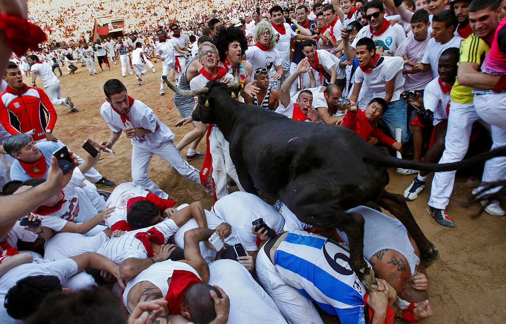 . AP10ThingsToSee - A bull jumps over revelers at the end of the fifth run of the famed San Fermin festival, in Pamplona, Spain on Thursday, July 11, 2013. One person has been hospitalized after several thousand people tested their speed and bravery by dashing with six fighting bulls through the streets of the northern Spanish city of Pamplona. (AP Photo/Alvaro Barrientos)