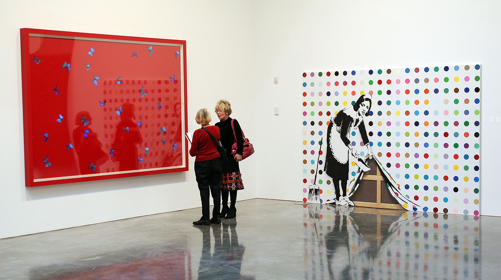 . Guests look at paintings by Damien Hirst (L) and Banksy on display during a press preview of the (RED) Auction to fight AIDS in Africa at the Gagosian Gallery on February 4, 2008 in New York City.  The auction will take place on Valentine\'s Day, February 14, 2008, at Sotheby\'s in New York.  (Photo by Scott Gries/Getty Images)