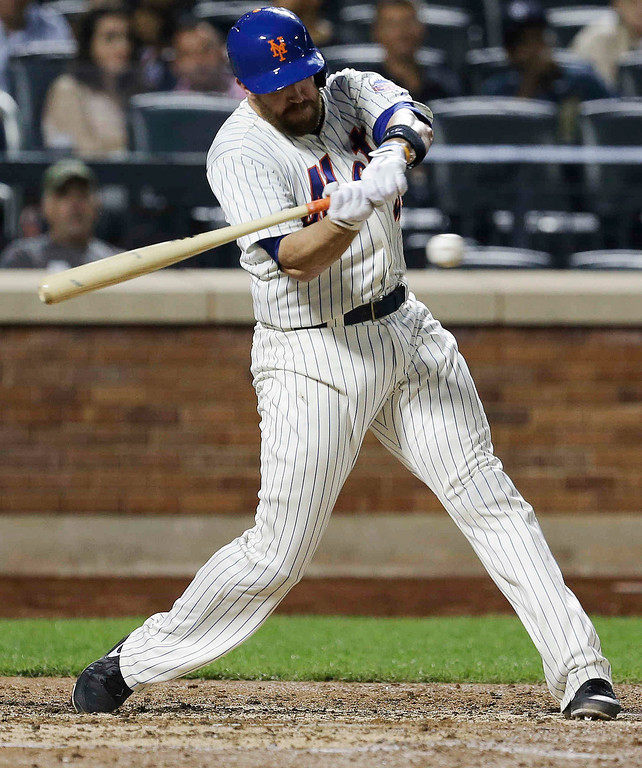 . New York Mets\' John Buck hits an RBI single during the fourth inning of a baseball game against the Colorado Rockies on Wednesday, Aug. 7, 2013, in New York. (AP Photo/Frank Franklin II)