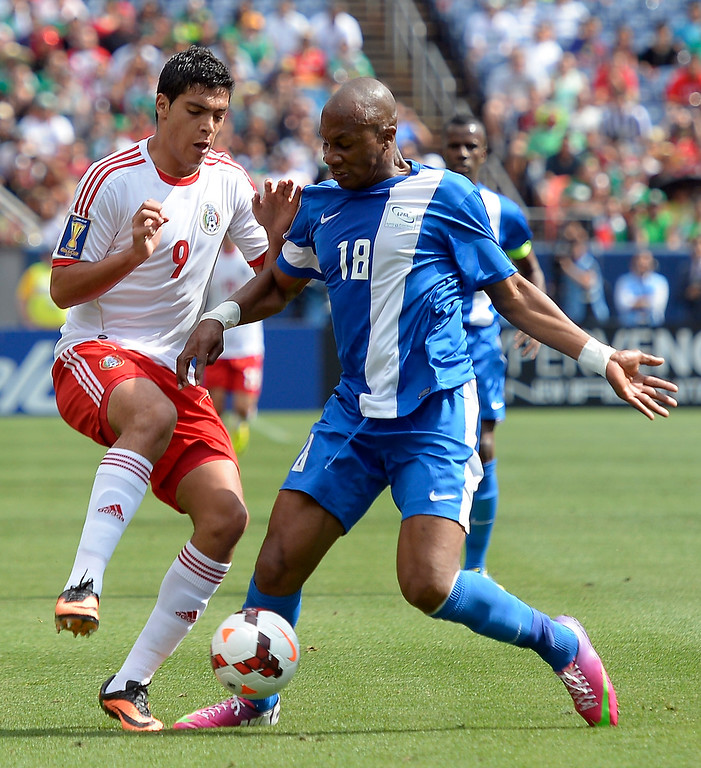 . Raul Jimenez #9 of Mexico battles for the bal with Juan Carlos Valenzuela #18 of Martinique during the first half of the CONCACAF Gold Cup soccer game July 14, 2013 at Sports Authority Field at Mile High. (Photo By John Leyba/The Denver Post)