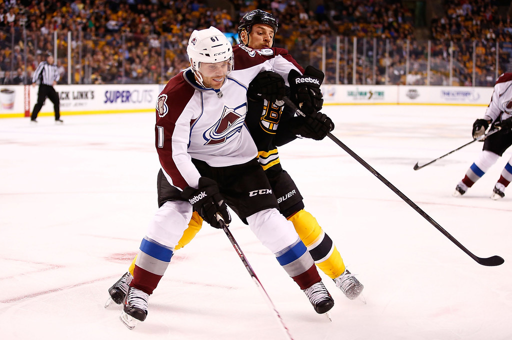 . Gregory Campbell #11 of the Boston Bruins and Andre Benoit #61 of the Colorado Avalanche battle for the puck in the first period during the game on October 10, 2013 at TD Garden in Boston, Massachusetts. (Photo by Jared Wickerham/Getty Images)