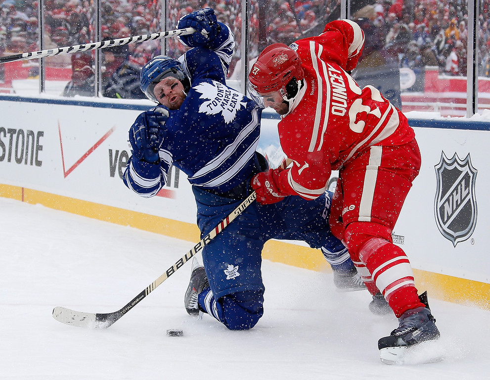 . Kyle Quincey #27 of the Detroit Red Wings and Phil Kessel #81 of the Toronto Maple Leafs battle for the puck during the first period of the  2014 Bridgestone NHL Winter Classic at Michigan Stadium on January 1, 2014 in Ann Arbor, Michigan. (Photo by Gregory Shamus/Getty Images)