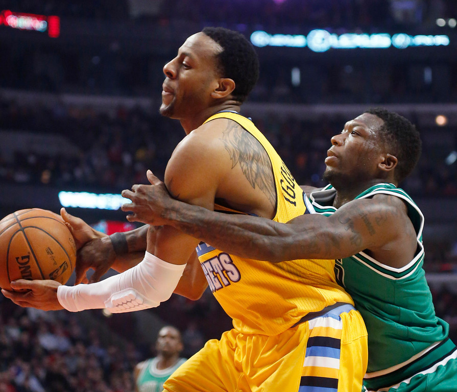 . Chicago Bulls guard Nate Robinson, right, fouls Denver Nuggets guard Andre Iguodala during the first half of an NBA basketball game, Monday, March 18, 2013, in Chicago. (AP Photo/Charles Rex Arbogast)