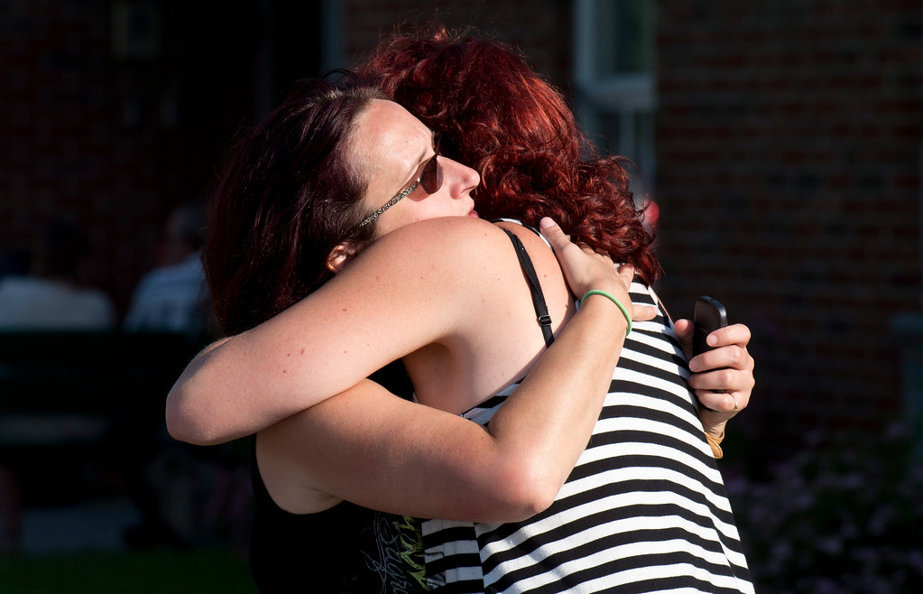 . Federique Mailloux hugs a friend as they wait outside an emergency center for news of friends following a train derailment in downtown Lac Megantic, Quebec, that caused explosions of railway cars carrying crude oil on Saturday, July 6, 2013. (AP Photo/The Canadian Press, Paul Chiasson)