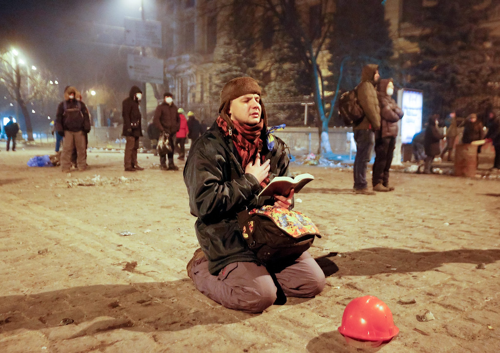 . A protester prays as he holds an open Bible during an anti-government protest in downtown Kiev, Ukraine, 21 January 2014.   EPA/SERGEY DOLZHENKO
