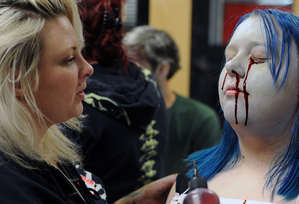 ". BOULDER, CO- FEBRUARY 19:  ""Zombie\"" Zoe Lloyd-Carpenter, 14, looks transformed by her make-up.  Make-up artist Danica Hughes, of Theatrical Costumes, Etc., applies blood that drips down her face.   With the help of a professional videographer, Fairview High School students produced a zombie video to advertise an Awareness Drive in Boulder Valley schools designed to bring attention to a variety of mental health and wellness issues.  Students were made to look like zombies by make-up artists from Theatrical Costumes, Etc. (Photo By Helen H. Richardson/ The Denver Post)"