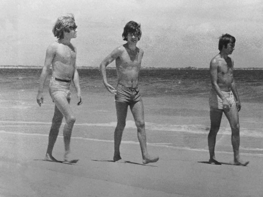 . Rolling Stones Brian Jones, Mick Jagger and Charlie Watts on the beach in Australia, 1965. (Photo by Central Press/Hulton Archive/Getty Images)