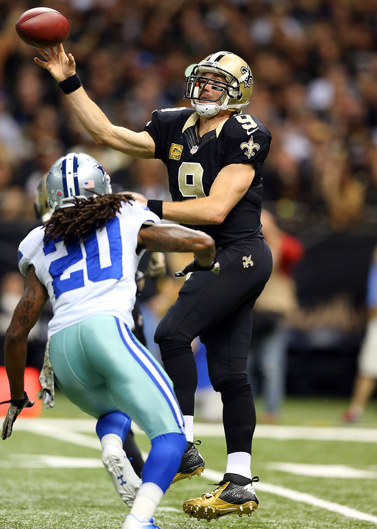 . Quarterback Drew Brees #9 of the New Orleans Saints passes as cornerback B.W. Webb #20 of the Dallas Cowboys defends during a game at the Mercedes-Benz Superdome on November 10, 2013 in New Orleans, Louisiana.  (Photo by Ronald Martinez/Getty Images)