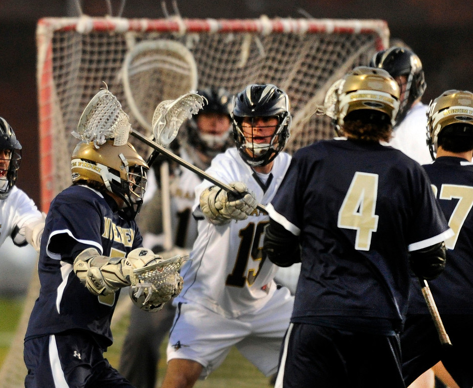 . LITTLETON, CO. - APRIL 10: Mustangs\' senior attack Austin Smith (5) looked for an opening in the first half. The Mullen High School boy\'s lacrosse team defeated Arapahoe 8-7 Wednesday night, April 10, 2013. Photo By Karl Gehring/The Denver Post)