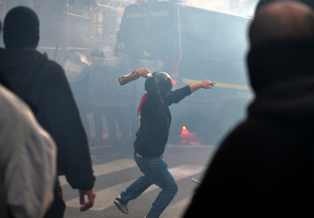 . A man throws a bottle in direction of policem during clashes on the sidelines of an anti-austerity protest on October 19, 2013 in Rome. Tens of thousands of people took to the streets in Italy and Portugal on Saturday to protest against budget cuts and the social cost of the economic crisis, amid concern over possible clashes in Rome. FILIPPO MONTEFORTE/AFP/Getty Images