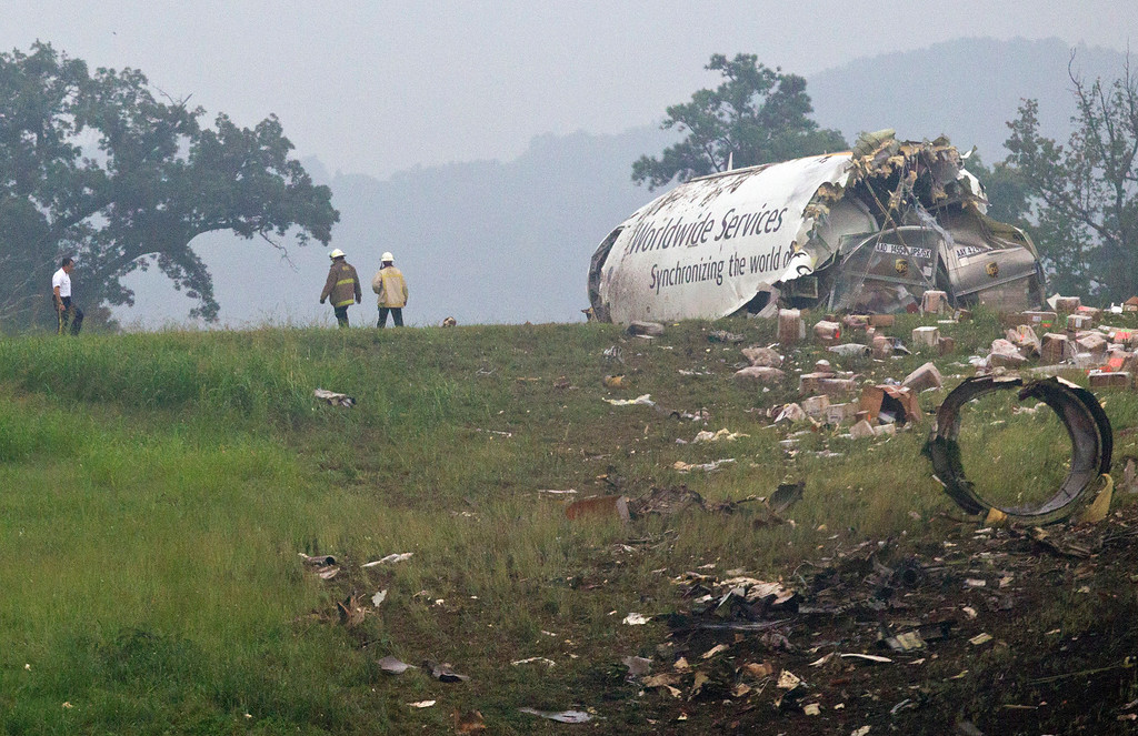 . Fire crews investigate where a UPS cargo plane lies on a hill at Birmingham-Shuttlesworth International Airport after crashing on approach, Wednesday, Aug. 14,  2013, in Birmingham, Ala. (AP Photo/Butch Dill)