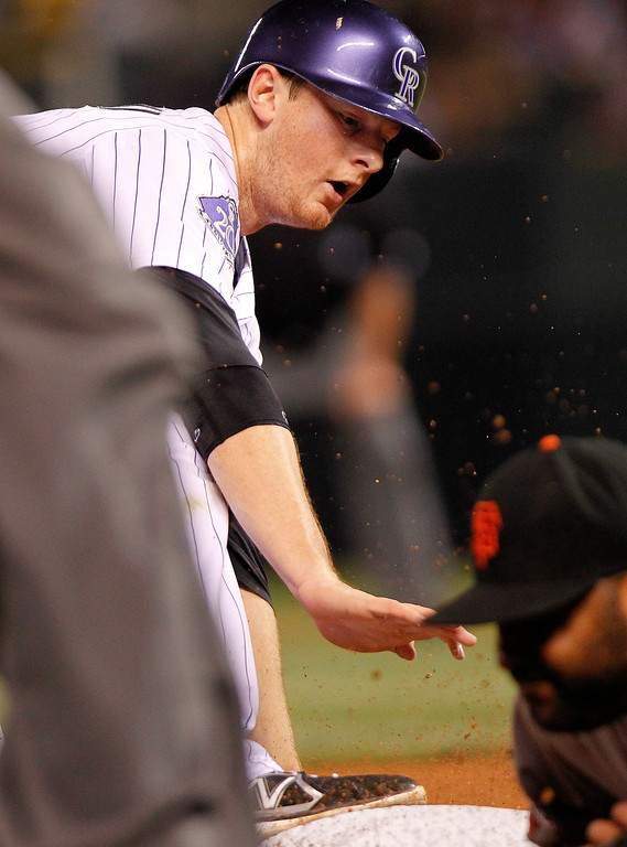. Colorado Rockies\' DJ LeMahieu steals third base during the sixth inning of a baseball game against the San Francisco Giants, Wednesday, Aug. 28, 2013, in Denver. (AP Photo/Barry Gutierrez)