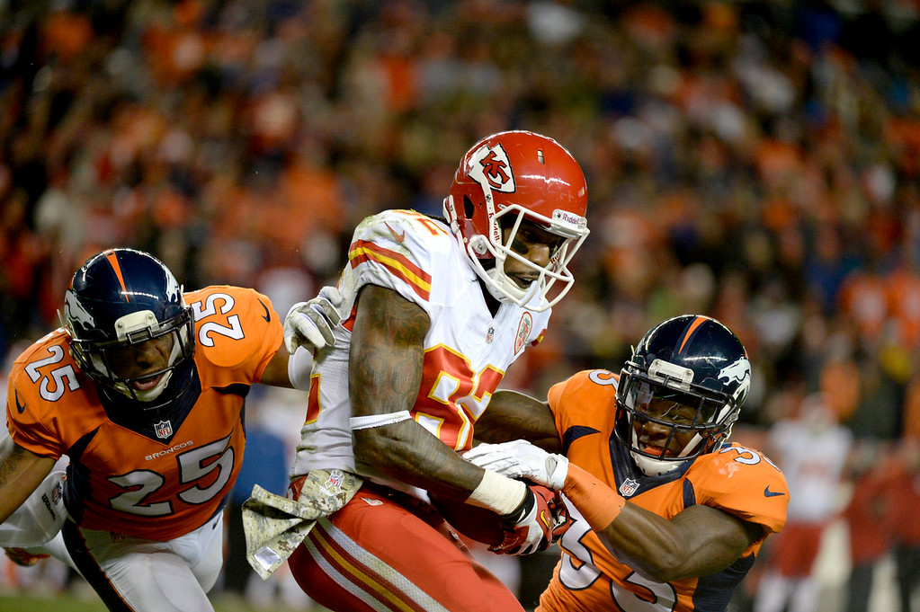 . Kansas City Chiefs wide receiver Dwayne Bowe (82) catches the ball against the defence of Denver Broncos strong safety Duke Ihenacho (33) and cornerback Chris Harris (25) during the second quarter. The Denver Broncos vs. the Kansas City Chiefs at Sports Authority Field at Mile High in Denver on November 17, 2013. (Photo by Tim Rasmussen/The Denver Post)