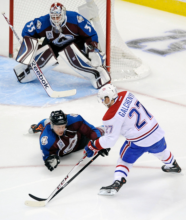 . Montreal Canadiens center Alex Galchenyuk, bottom right, tries to shoot the puck against Colorado Avalanche goalie Jean-Sebastien Giguere, top, as Colorado defenseman Erik Johnson,  bottom left, dives in front of the goal in the first period of an NHL hockey game on Saturday, Nov. 2, 2013, in Denver.  (AP Photo/Chris Schneider)