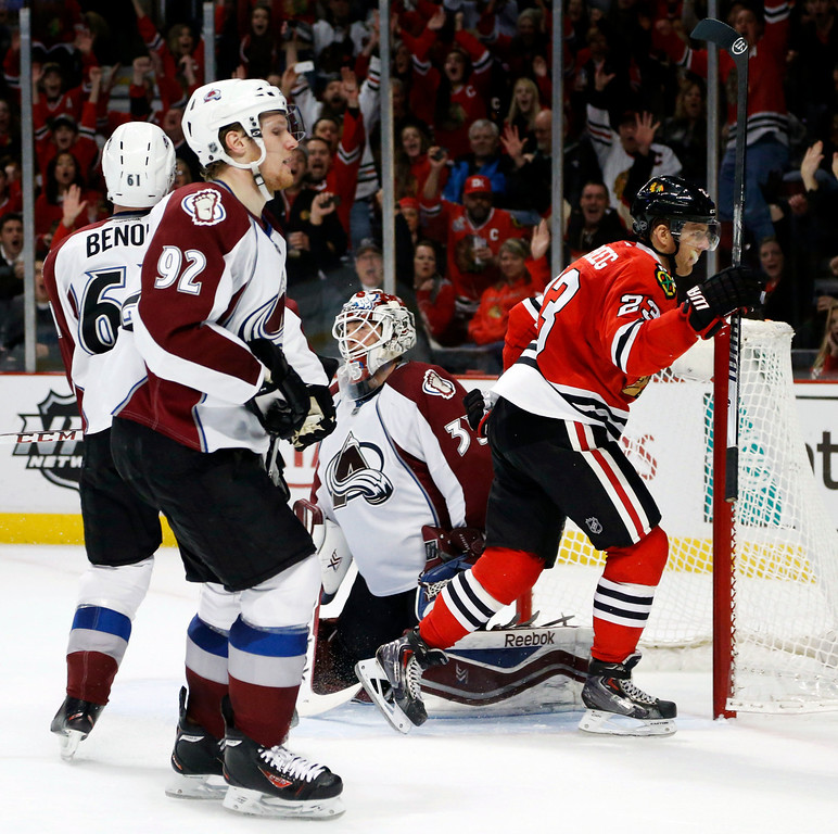 . Chicago Blackhawks right wing Kris Versteeg (23) celebrates his goal past Colorado Avalanche goalie Jean-Sebastien Giguere (35) Andre Benoit (61) and Gabriel Landeskog (92) during the second period of an NHL hockey game Friday, Dec. 27, 2013, in Chicago. (AP Photo/Charles Rex Arbogast)