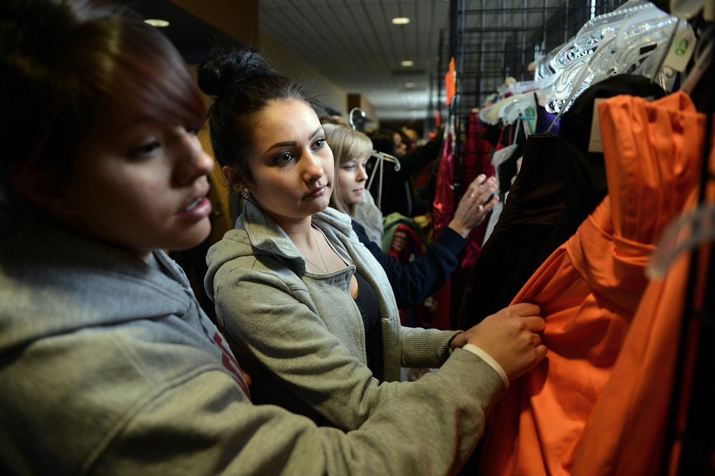 ". COMMERCE CITY, CO. - MARCH 16: Alicia Chavez, left, and Mickaelas Mader, both seniors at North High School, look through the selection at the Prom Dress Exchange Corp. event in Commerce City, CO March 16, 2013. With a valid student ID and a suggested $10 donation, teenage girls could chose from 1,356 donated dresses that lined a long hallway at Dick�s Sporting Goods Park. Chavez said prom is expensive, ""this is awesome, we can spend our money on other stuff.\"" (Photo By Craig F. Walker/The Denver Post)"