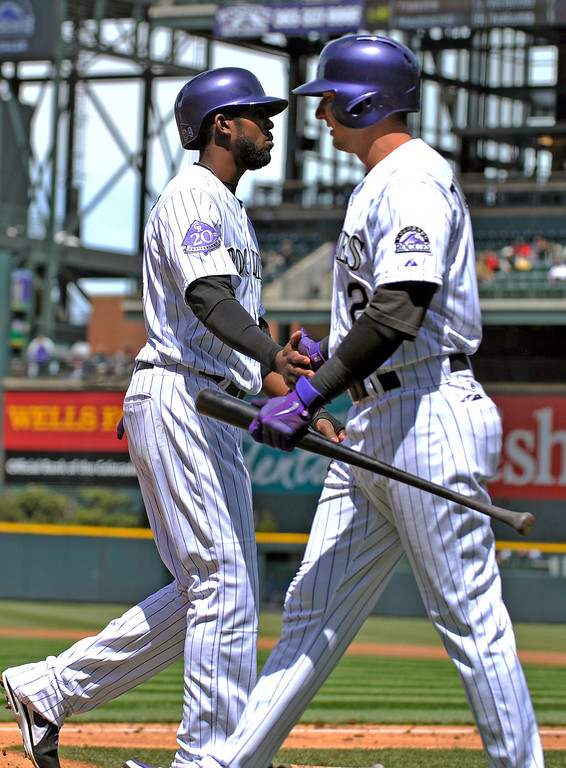 . Colorado Rockies\' Dexter Fowler (24) is congratulated by teammate Troy Tulowitzki (2), right, after scoring against the New York Mets during the first inning of a baseball game on Thursday, April 18, 2013, in Denver. (AP Photo/Jack Dempsey)