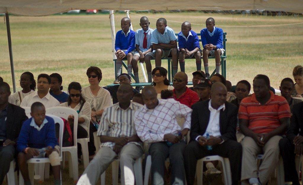 . Kenyan schoolboys sit on a stand to listen as friends and relatives of those who died attend a memorial service and tree-planting marking the one-month anniversary of the Sept. 21 Westgate Mall terrorist attack, in Karura Forest in Nairobi, Kenya Monday, Oct. 21, 2013. (AP Photo/Ben Curtis)