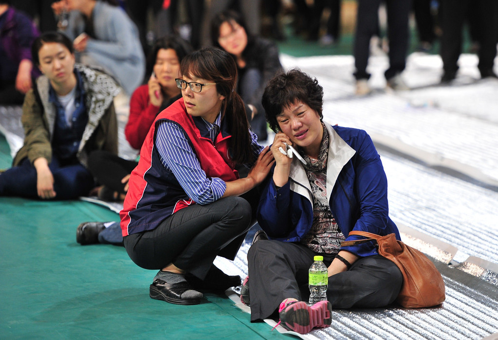 . South Korean relatives of missing people react as they gather at a gym in Jindo on April 16, 2014 as rescue teams, including elite navy SEAL divers, raced to find up to 293 people missing from a capsized ferry carrying 459 passengers and crew -- mostly high school students bound for a holiday island.  Two people -- a male student and a female crew member -- were confirmed dead as the vessel sank 20 kilometres (13 miles) off the southern island of Byungpoong.  AFP PHOTO / JUNG YEON-JE/AFP/Getty Images