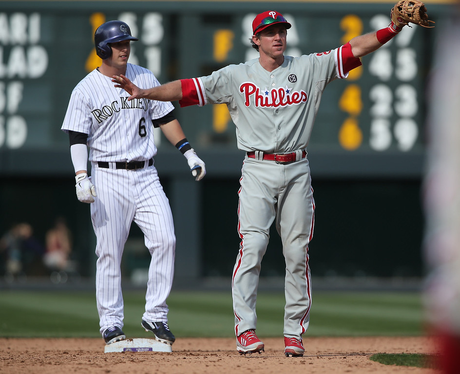 . Philadelphia Phillies second baseman Chase Utley, front, calls for a review of a play as Colorado Rockies\' pinch-hitter Corey Dickerson looks on from second base in the sixth inning of the Phillies\' 10-9 victory in a baseball game in Denver on Sunday, April 20, 2014. After the umpires reviewed the play, Dickerson was called out. (AP Photo/David Zalubowski)