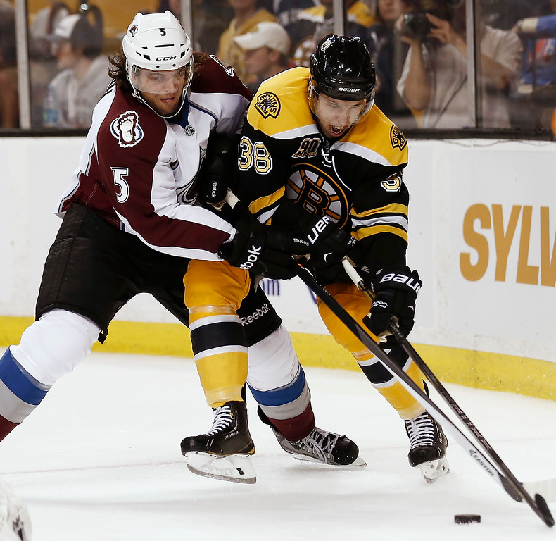 . Boston Bruins\' Jordan Caron (38) and Colorado Avalanche\'s Nate Guenin vie for the puck during the second period of an NHL hockey game in Boston on Thursday, Oct. 10, 2013. (AP Photo/Winslow Townson)
