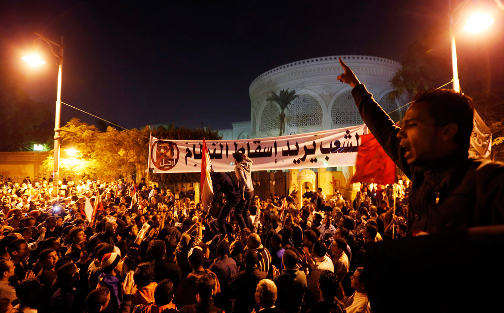 ". Protesters chant slogans during a demonstration in front of the presidential palace in Cairo, Egypt, Sunday, Dec. 9, 2012.  Egypt\'s liberal opposition called for more protests Sunday, seeking to keep up the momentum of its street campaign after the president made a partial concession overnight but refused its main demand he rescind a draft constitution going to a referendum on Dec. 15. Arabic on the banner, background, reads, ""the people want to end the regime.\""(AP Photo/Petr David Josek)"
