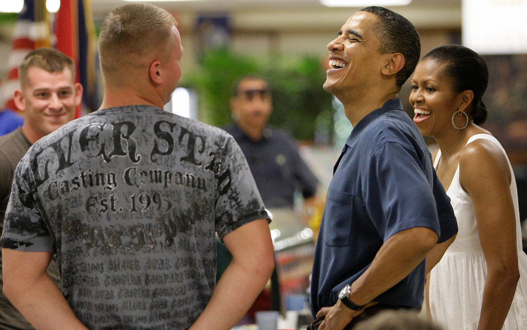 . President Barack Obama, and first lady Michelle Obama, laugh as they greet marines during Christmas dinner at Anderson Hall on Marine Corps Base Hawaii in Kailua, Hawaii  Friday, Dec. 25, 2009. The Obamas were in Hawaii for the holidays.  (AP Photo/Alex Brandon)