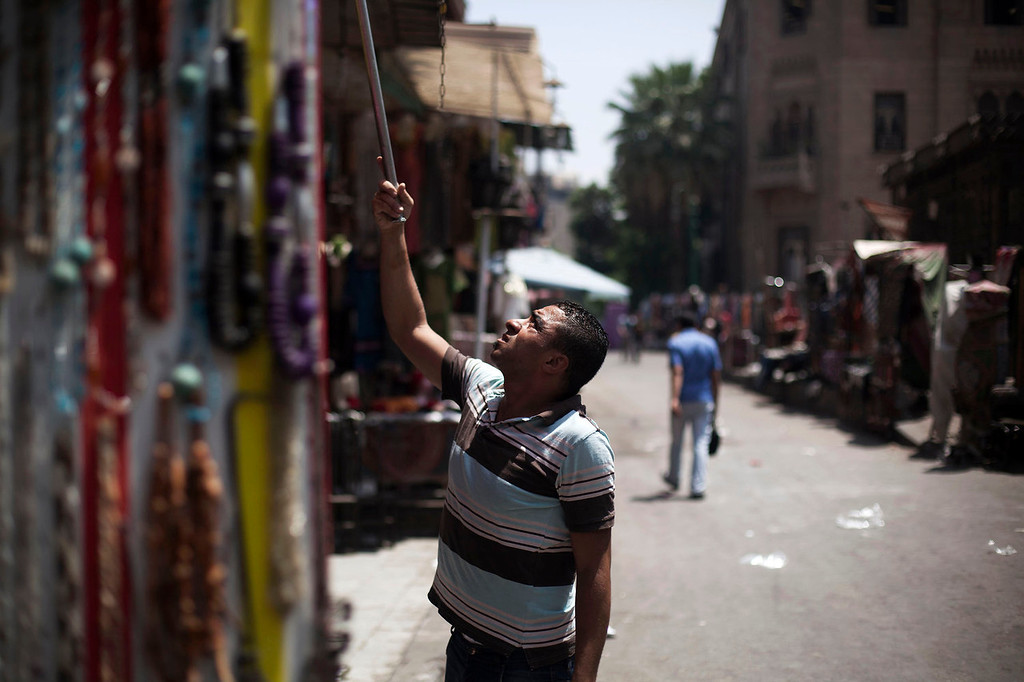 . An Egyptian vendor hangs his stuff outside his souvenir store in the Khan El-Khalili market, normally a popular tourist destination, in Cairo, Egypt, Wednesday, Aug. 21, 2013. Riots and killings that erupted across the country after the crackdown against followers of ousted President Mohammed Morsi have delivered a severe blow to Egypt\'s tourism industry, which until recently accounted for more than 11 percent of the country\'s gross domestic product and nearly 20 percent of its foreign currency revenues. (AP Photo/Manu Brabo)