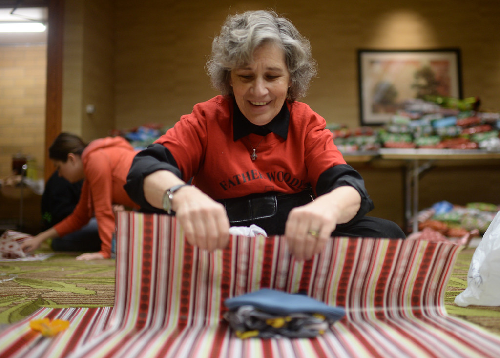 """. DENVER, CO. DECEMBER 21: Regis University  professor Victoria McCabew is wrapping Christmas gift during the annual Father Woody Christmas Party in Denver, Colorado December 21, 2013. In advance of handing out 5,000 gifts, volunteers are doing a \""""wrapping party\"""" at the Sheraton Denver Downtown Hotel. (Photo by Hyoung Chang/The Denver Post)"""