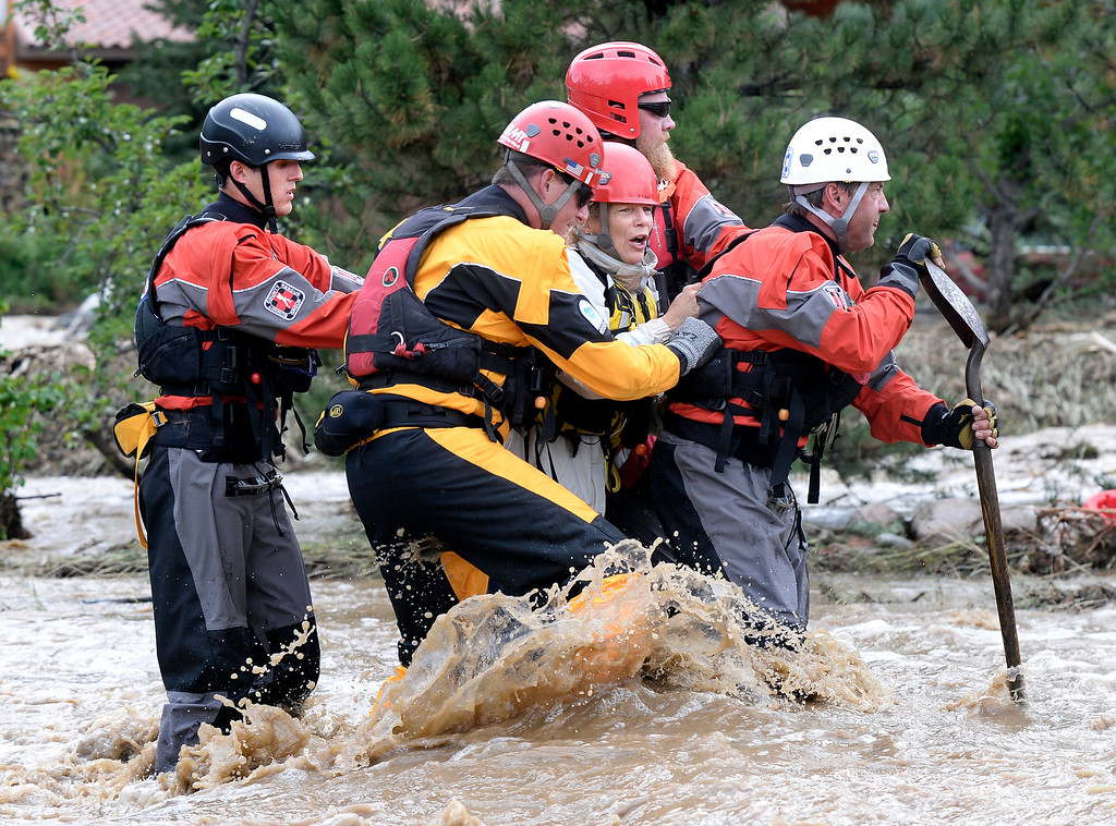 . The Summit County Rescue team works to save Suzanne Sophocles, center, from her severely flooded home Friday, Sept. 13, 2013 in Boulder, Colo. By truck and helicopter, thousands of people stranded by floodwaters came down from the Colorado Rockies on Friday, two days after seemingly endless rain turned normally scenic rivers and creeks into coffee-colored rapids that wrecked scores of roads and wiped out neighborhoods. (AP Photo/The Daily Camera, Jeremy Papasso) NO SALES