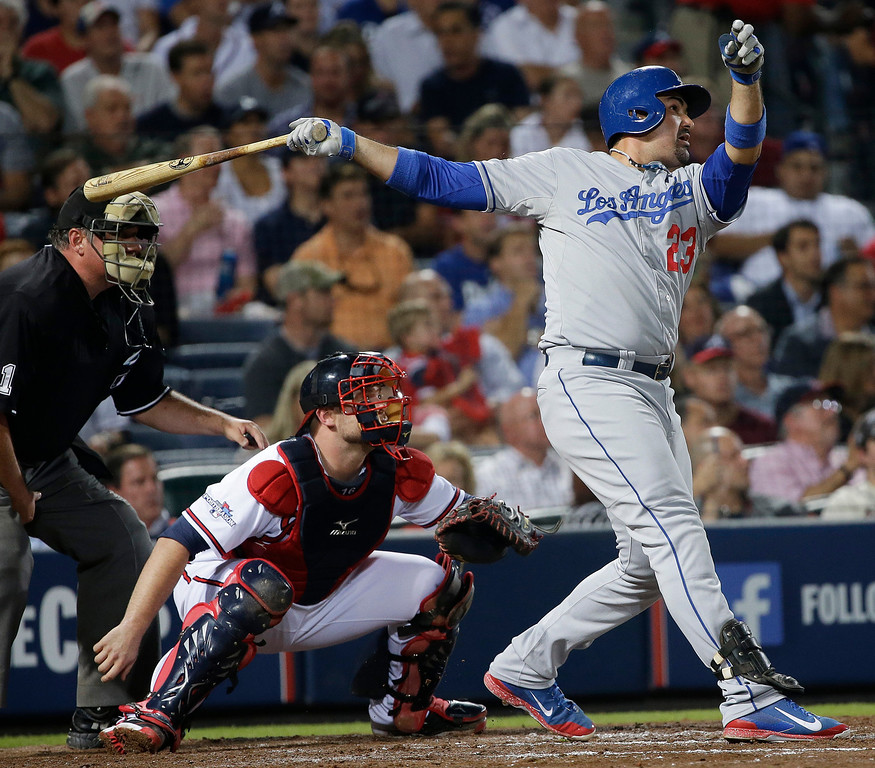 . Los Angeles Dodgers\' Adrian Gonzalez (23) watches his two-run home run against the Atlanta Braves in the third inning of Game 1 of the National League Divisional Series, Thursday, Oct. 3, 2013, in Atlanta. (AP Photo/John Bazemore)