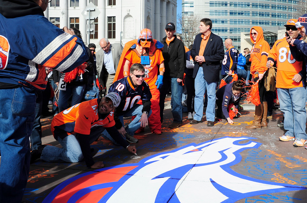 . At left, Denver Mayor Michael Hancock and Governor John Hickenlooper sign Bannock Street using chalk, during a rally to send off the Denver Broncos, at the City and County Building in Denver, Colorado, Sunday, January 26, 2014. The noon rally brought out scores of supporters and included an appearance by Governor John Hickenlooper and Denver Mayor Michael Hancock.  (Photo By Brenden Neville / Special to The Denver Post)