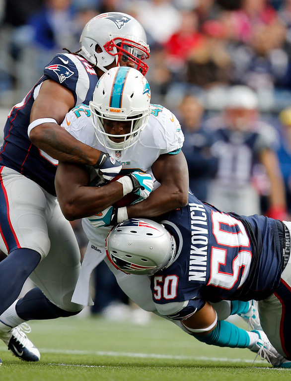 . New England Patriots linebackers Dont\'a Hightower, left, and Rob Ninkovich (50) tackle Miami Dolphins tight end Charles Clay (42) in the first quarter of an NFL football game Sunday, Oct. 27, 2013, in Foxborough, Mass. (AP Photo/Michael Dwyer)