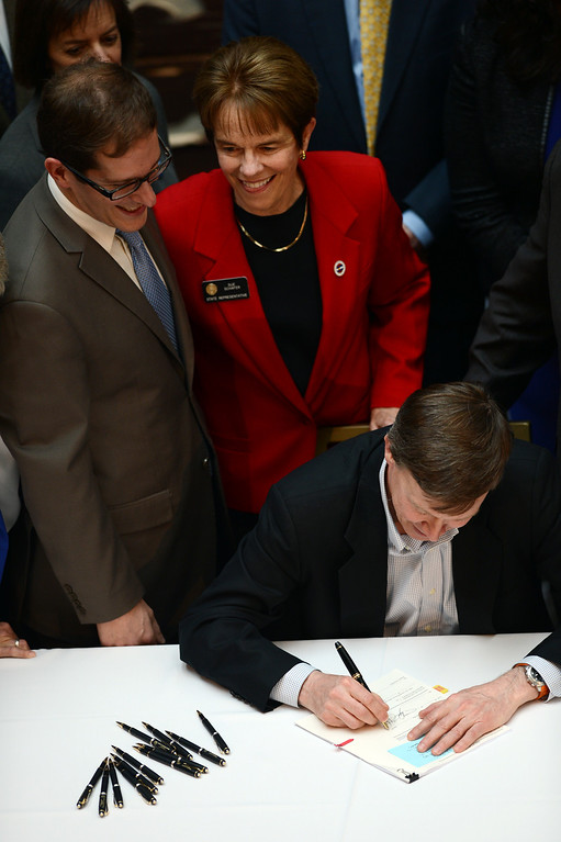 . DENVER, CO. - MARCH 21: Colorado Gov. John Hickenlooper, bottom, signs Senate Bill 11 legalizing civil unions with Speaker of the Colorado House of Representatives Mark Ferrandino, top left, and Rep. Sue Schafer, top right. Crowds packed History Colorado Center on Thursday, March 21, 2013. (Photo By Hyoung Chang/The Denver Post)