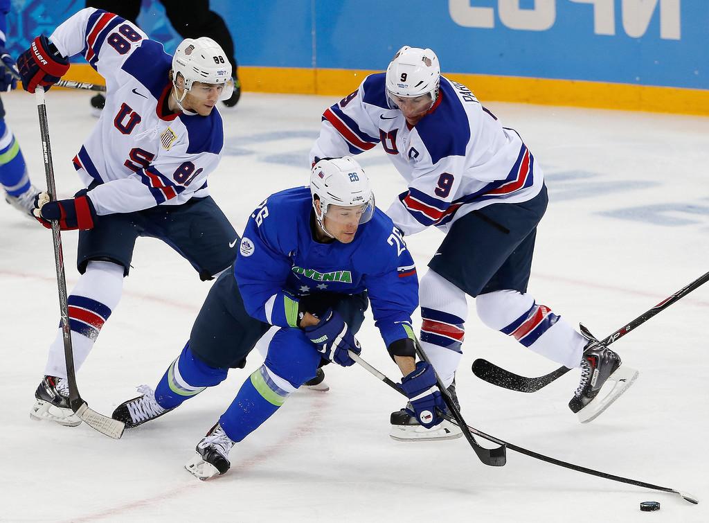 . Slovenia forward Jan Urbas (26) take control of the puck from USA forward Patrick Kane (88) and USA forward Zach Parise (9) during the 2014 Winter Olympics men\'s ice hockey game at Shayba Arena Sunday, Feb. 16, 2014, in Sochi, Russia. (AP Photo/Petr David Josek)