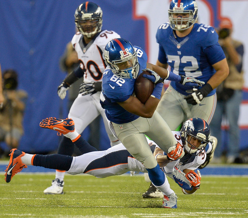 . New York Giants wide receiver Rueben Randle (82) picks up a few yards before he is tripped up by Denver Broncos defensive back Tony Carter (32) during the third quarter September 15, 2013 MetLife Stadium. (Photo by John Leyba/The Denver Post)