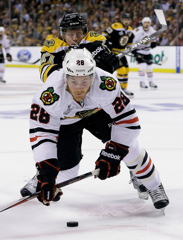 . Boston Bruins defenseman Torey Krug (47) checks Chicago Blackhawks right wing Ben Smith (28) to the ice during the first period in Game 3 of the NHL hockey Stanley Cup Finals in Boston, Monday, June 17, 2013. (AP Photo/Elise Amendola)