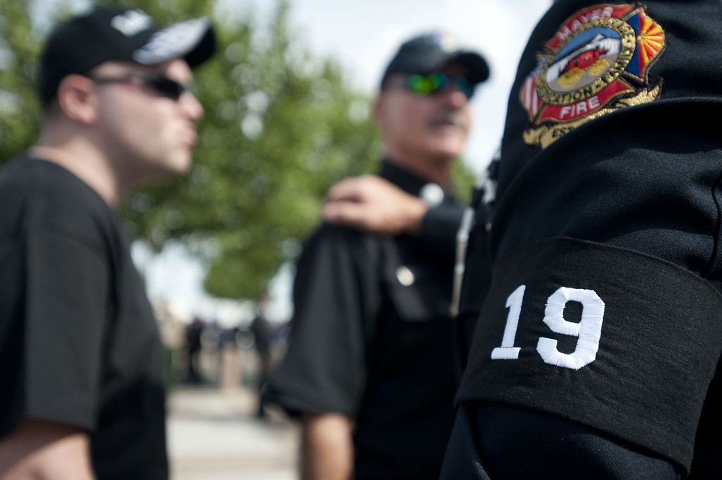 . Chaplain Bob Ossler with the Mayer, Arizona fire department wears a black arm band with the number 19 at the entrance to a memorial service honoring the 19 firefighters killed in a wildfire at Tim\'s Toyota Center July 9, 2013 in Prescott Valley, Arizona. (Photo by Laura Segall/Getty Images)